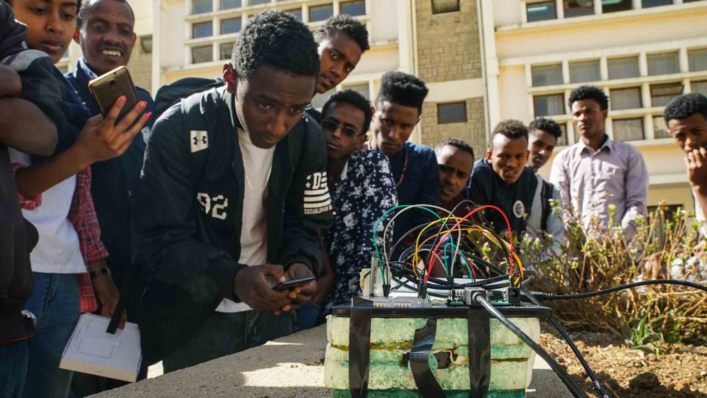 At Mekelle University, Girmay Araya, 20, demonstrates his team's model AI tractor in a flower bed. [Visual: Alice McCool for Undark]